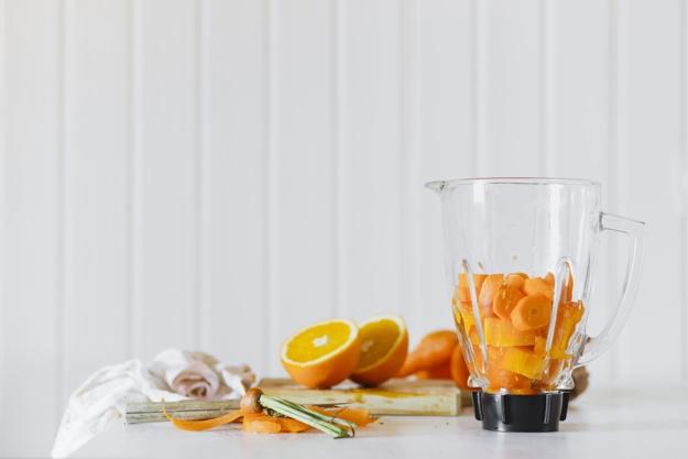 Blender avec des fruits coupés près d'orange
