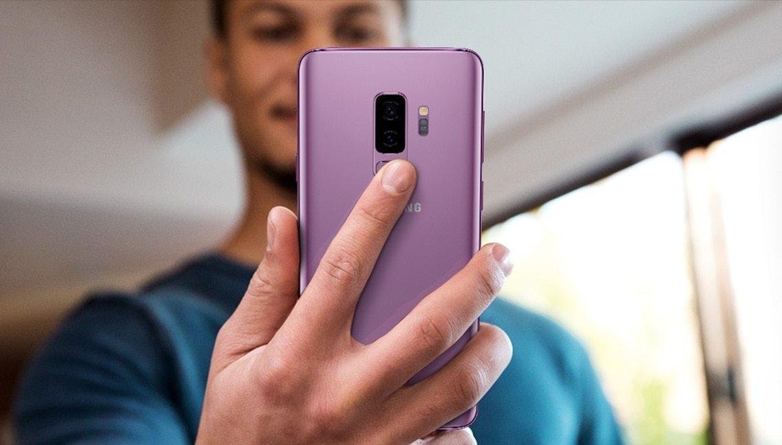 Photo d'une personne tenant un Galaxy S9+ pour montrer le positionnement du capteur d'empreinte digitale.