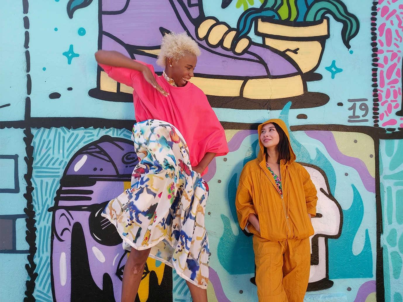 Photo capturée par l'objectif grand angle du Galaxy A80 composé de deux femmes, l'une haute et l'autre courte, devant un mur de graffitis.