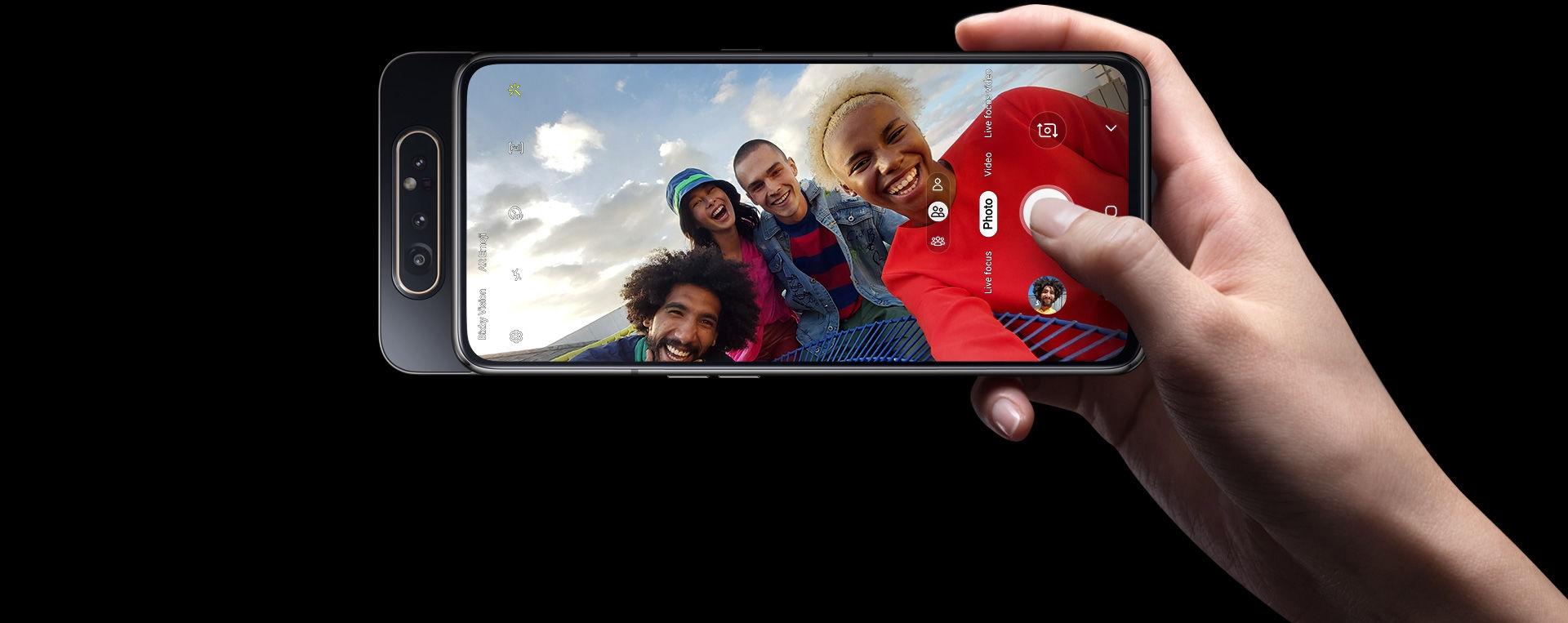 Main droite prenant un groupe avec la caméra rotative 48MP de Galaxy A80.