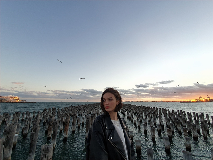 Photo capturée par Galaxy S10 plus d'une femme debout devant plusieurs poteaux en bois dans la mer au crépuscule.  Il se retire pour montrer plus de la scène, avec la caméra ultra grand angle.