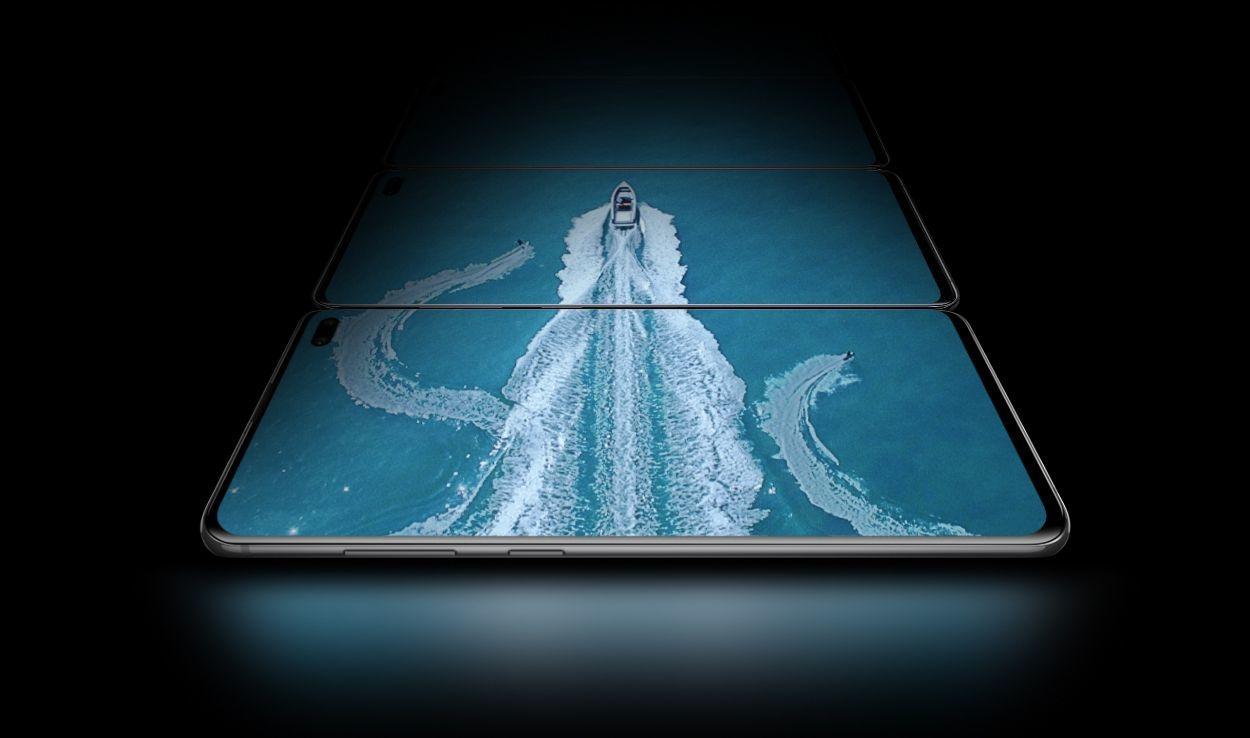 Trois téléphones Galaxy S10 plus en mode paysage, posés à plat au-dessus de celui qui le précède, vus sous un léger angle depuis le côté du bouton Bixby and Volume.  Sur les trois écrans, il y a une vue aérienne d'un bateau dans l'eau avec deux skieurs nautiques, montrant l'étendue de l'écran Infinity-O Display.