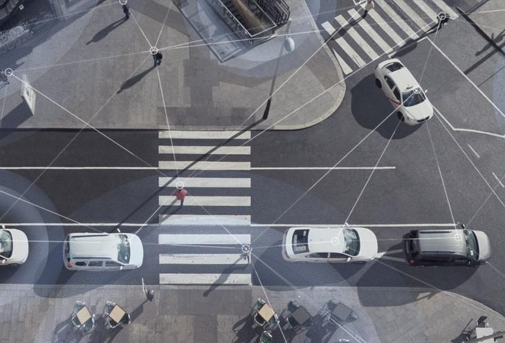 Photo aérienne d'une scène de rue avec des voitures conduisant et des personnes marchant, avec des lignes superposées pour montrer la connectivité du Wi-Fi et du LTE.
