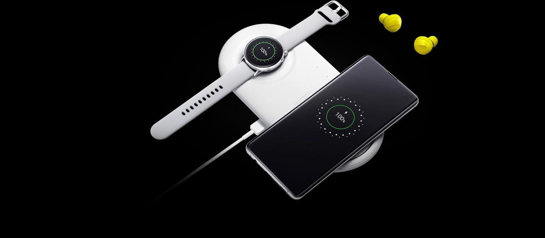 Photo de Galaxy Buds à côté de Galaxy Watch Active et de Galaxy S10 avec chargement sur le chargeur sans fil Duo Pad, avec l'interface de chargement affichée sur les écrans des deux appareils.